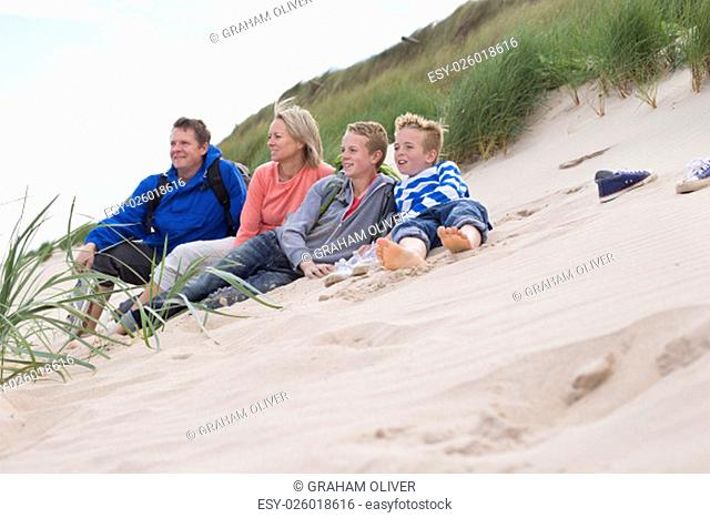 Family of four sitting on the sand dunes. They are wearing warm, casual clothing and looking out to sea