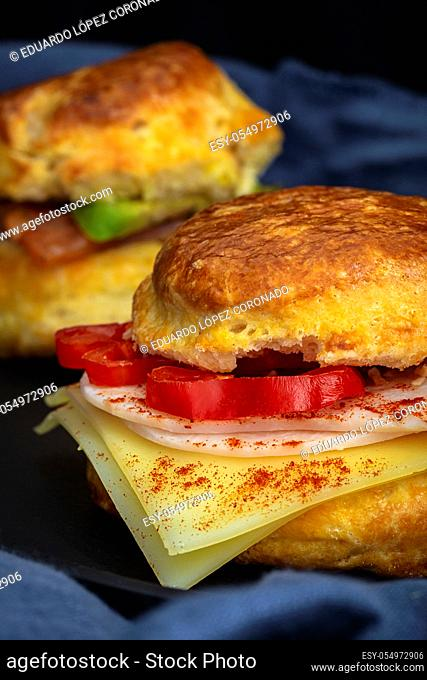 Assortment of homemade scones with ham, cheese, avocado, salmon, cream cheese and strawberry jam on black background. Traditional english food
