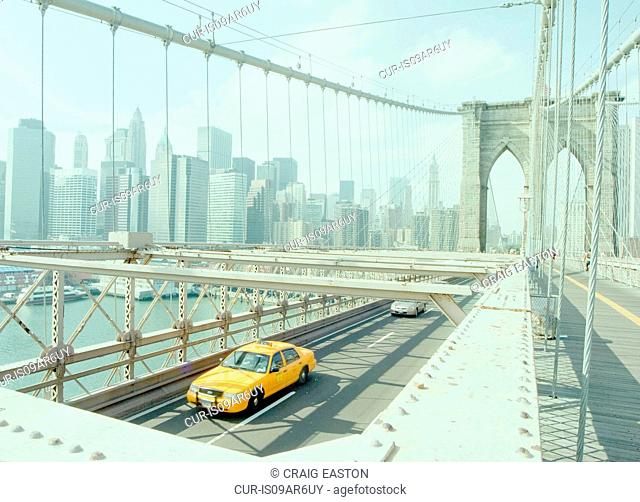 Yellow taxi crossing Brooklyn Bridge, New York, USA