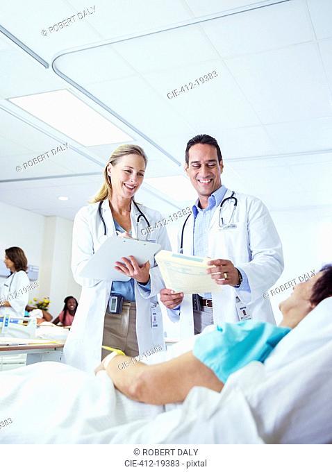 Doctors examining patient in hospital room