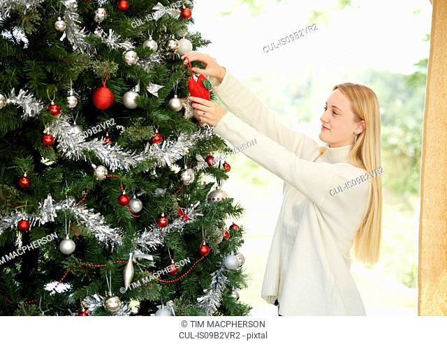 Teenage girl hanging decorations on christmas tree
