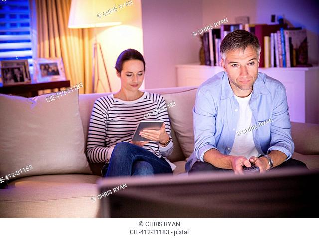 Wife using digital tablet next to husband watching TV in living room