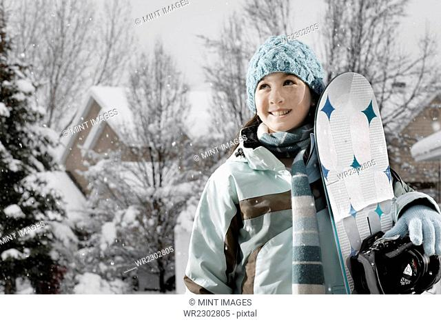 Winter snow. A girl carrying a snowboard