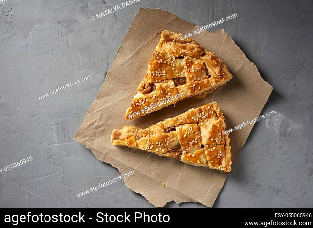 two baked pieces of apple pie on brown paper, top view, gray background
