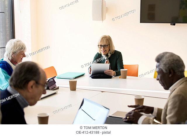 Senior businesswoman using digital tablet, leading conference room meeting