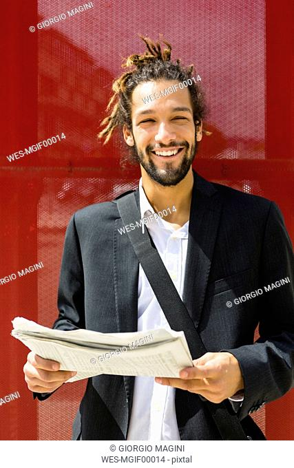 Portrait of young businessman with dreadlocks reading newspaper
