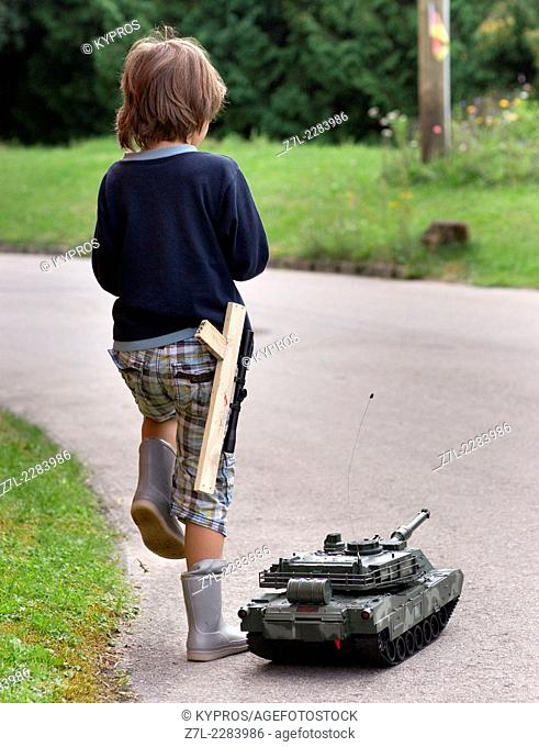 Eight year old boy playing with radio controlled toy tank