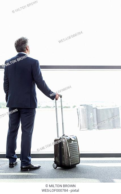 Businessman at the airport looking out of window