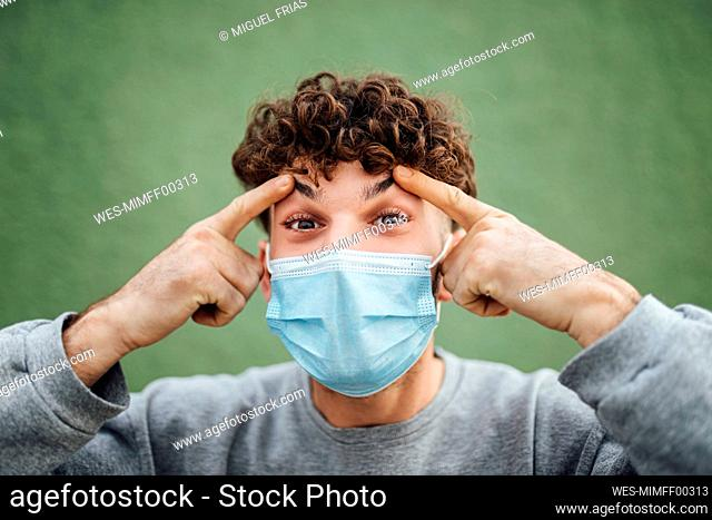 Young man touching eyebrows against green background in studio during COVID-19