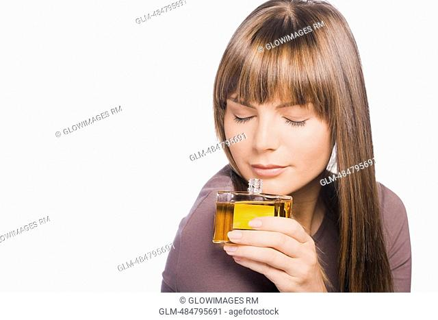 Close-up of a young woman smelling perfume