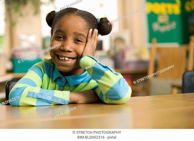 African girl in classroom with head in hands