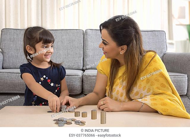 Smiling mother and daughter stacking coins sitting together