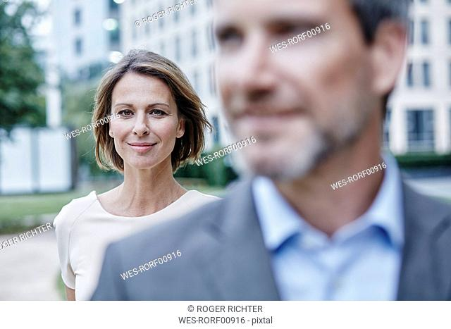Portrait of confident businesswoman and businessman outdoors