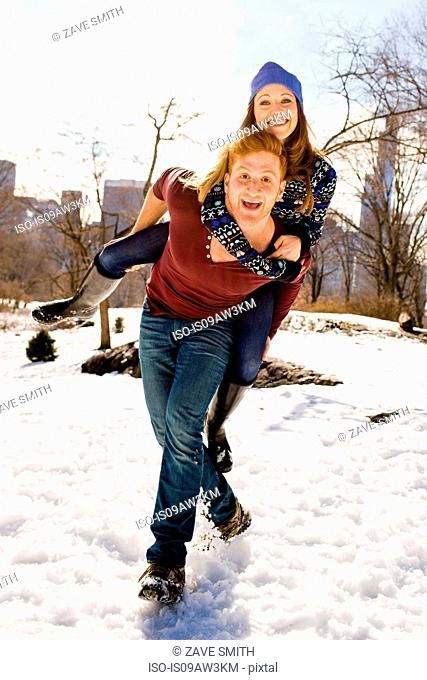 Young man giving girlfriend a piggy back in snowy Central Park, New York, USA
