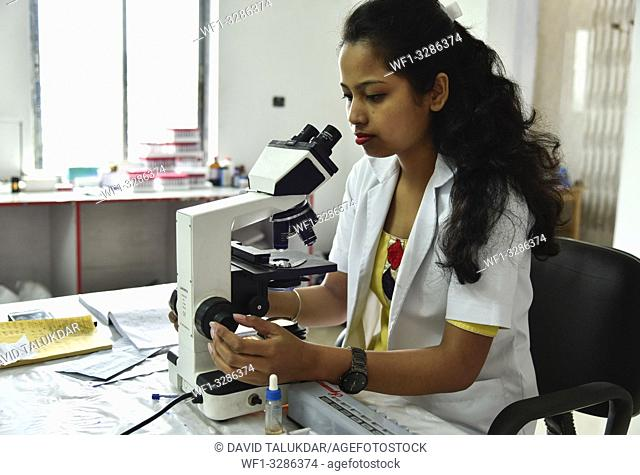 Guwahati, Assam, India. April 6, 2019. Laboratory technician looking blood samples by a Microscope in the eve of World Health Day in Guwahati