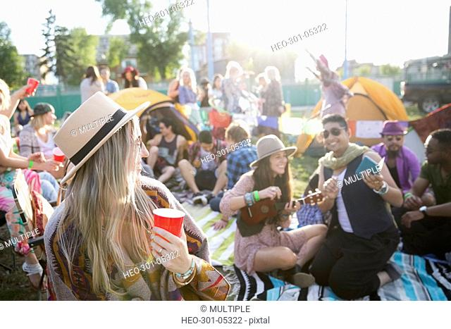 Young friends hanging out and drinking at summer music festival campsite
