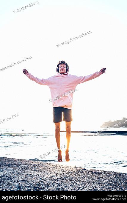 Carefree young man jumping at beach