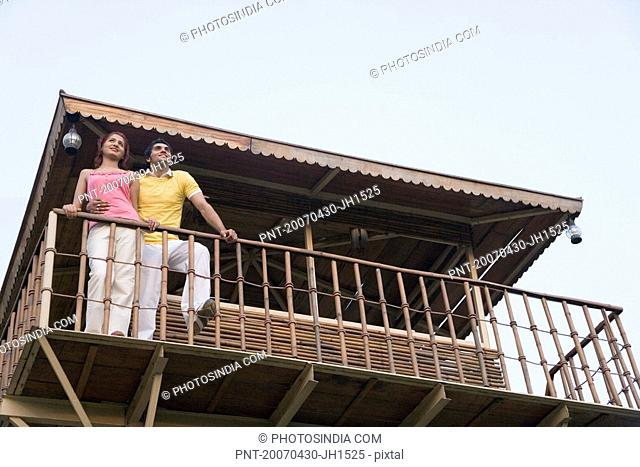 Low angle view of a young couple standing on the beach hut