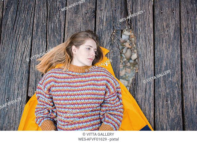 Serious young woman lying on boardwalk looking away