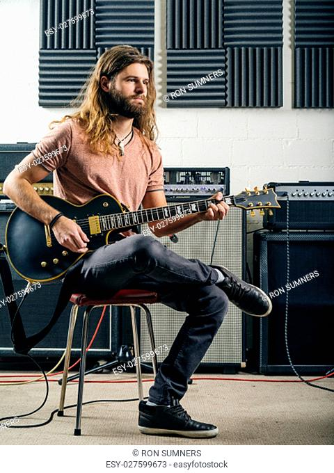 Photo of a young man with long hair and beard playing electric guitar in a recording studio