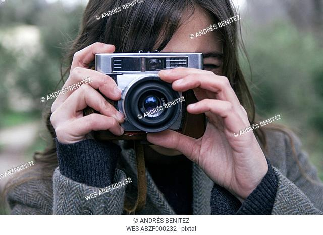 Woman taking a photo with an analog camera