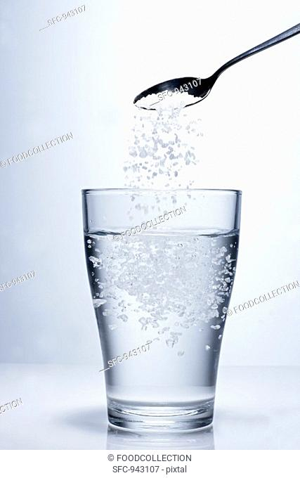 Sprinkling salt into a glass of water
