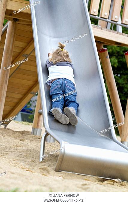 Germany, Girl playing on slide