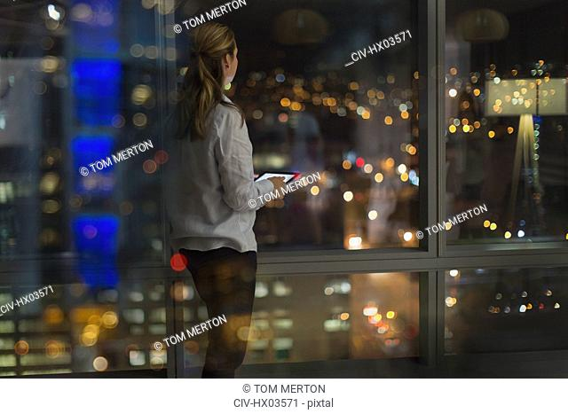 Pensive businesswoman with digital tablet working late, looking out urban office window at night