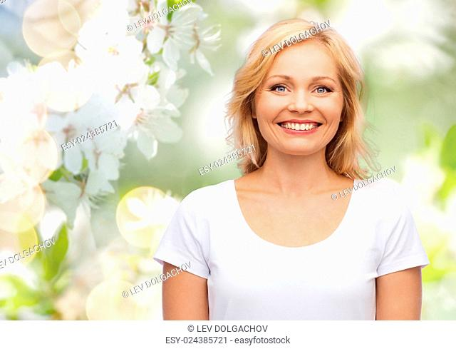 happiness and people concept - smiling woman in blank white t-shirt over natural spring cherry blossom background