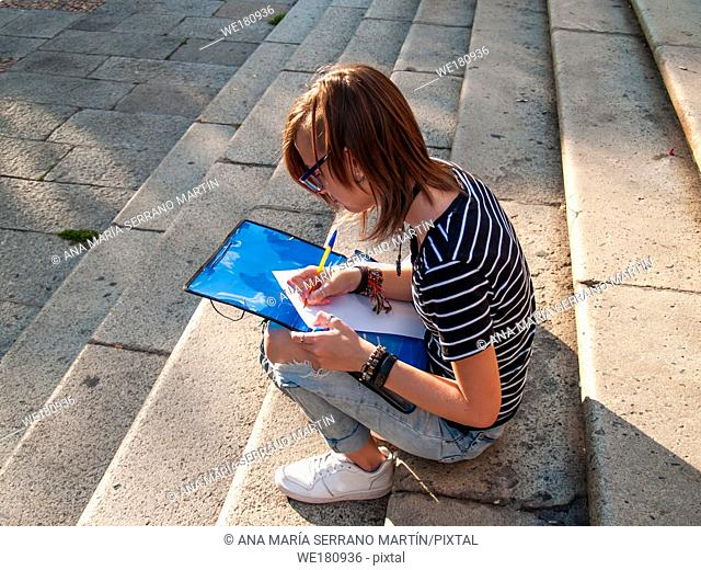 A teenage woman writing with a pen in a folio on a folder sitting in the stairs on a university campus