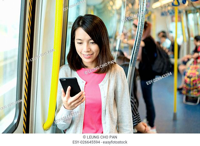 Woman use of mobile phone at train compartment