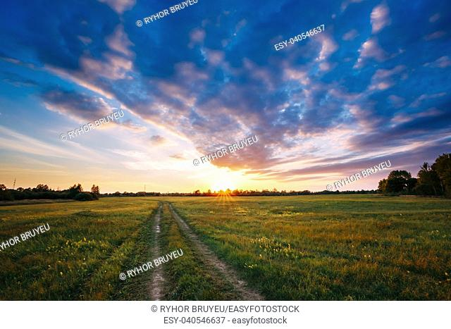Sunset, Sunrise Over Rural Meadow Field. Bright Dramatic Sky And Country Road Path Way. Countryside Landscape Under Scenic Summer Dramatic Sky In Sunset Dawn...