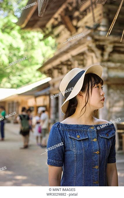 Young woman wearing blue dress and hat at Shinto Sakurai Shrine, Fukuoka, Japan