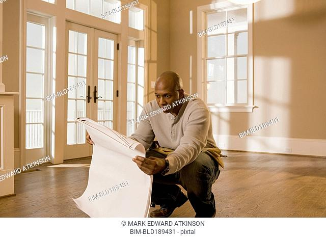 African man holding blueprint