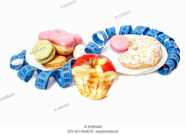 new diet concept, question sign in shape of measurment tape between red apple and donut, cake, macaroon isolated on white, hard choice food
