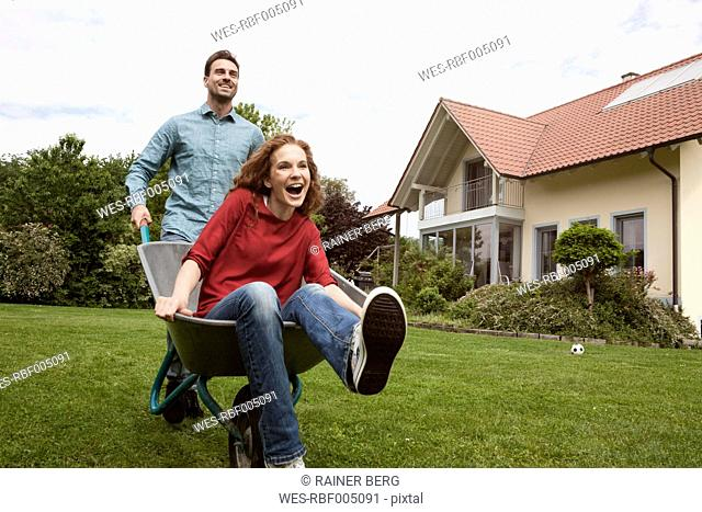 Man pushing happy woman in wheelbarrow in garden