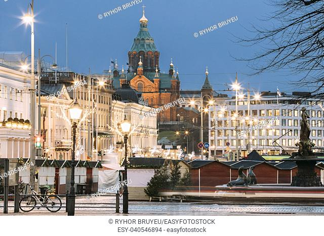 Helsinki, Finland. Uspenski Cathedral In Evening Or Night Illuminations Lights And Christmas Market On Market Square. Eastern Orthodox Cathedral Dedicated To...