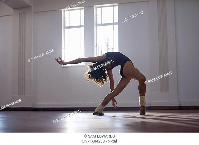 Graceful, flexibility young female dancer practicing in dance studio