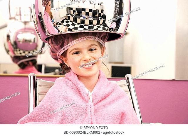 portrait of young girl sitting under hair dryer