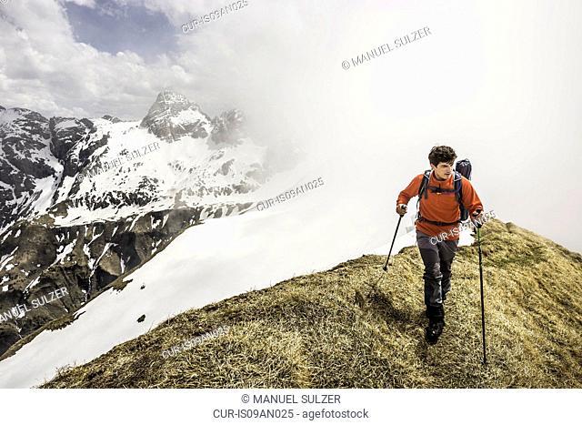 Young man mountain trekking along ridge in Bavarian Alps, Oberstdorf, Bavaria, Germany