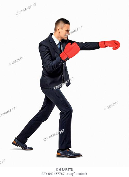 A businessman stands in side view on white background and throws punches wearing red boxing gloves. Fight for promotion. Career path