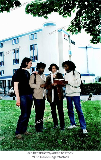 Paris, France, Group of Mixed Race and Gender, French Teens Looking at Tourist Guide Book Outside Hotel