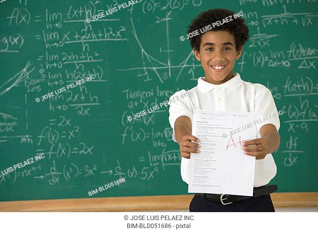 Hispanic boy holding school paper with A plus grade