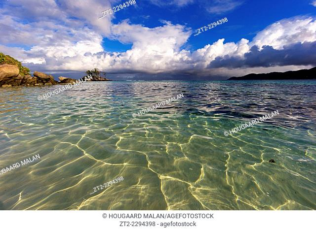 Landscape view of rain clouds over a crystal clear beach. Anse Royale, Mahe, Seychelles