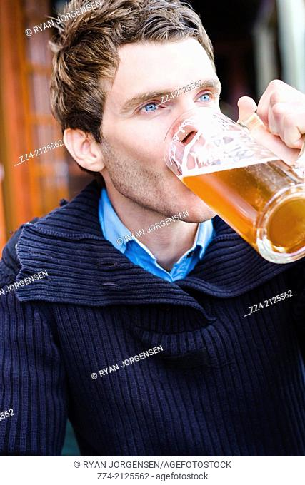 Tilted unposed photograph of a European man enjoying a cold beer at a German pub while travelling Germany for Oktoberfest. Candid travel photograph