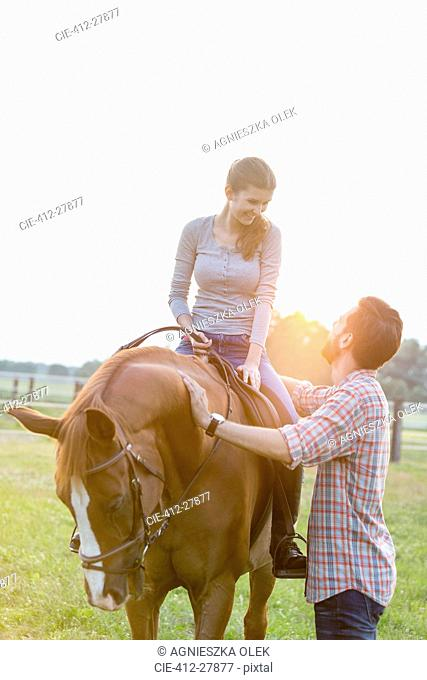 Smiling couple horseback riding in rural pasture