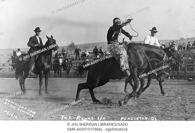 African-American cowboys riding horses in a rodeo area, with spectators and other participants in the background, at the first annual Pendleton Round-Up