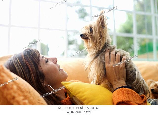 Woman in her late 30s playing with her dog
