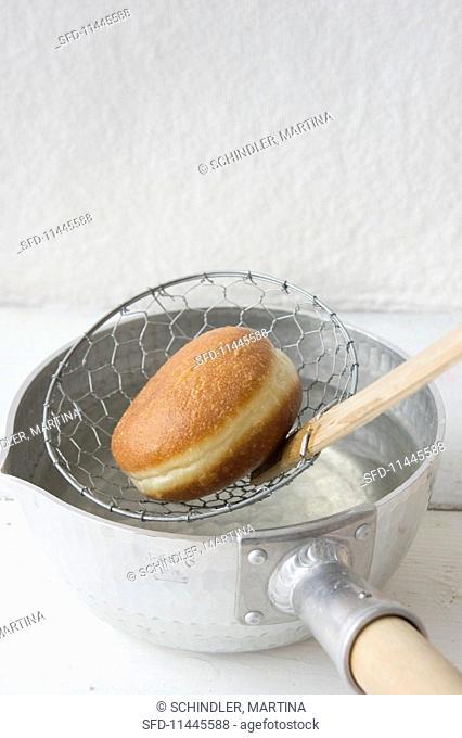 A doughnut frying in oil