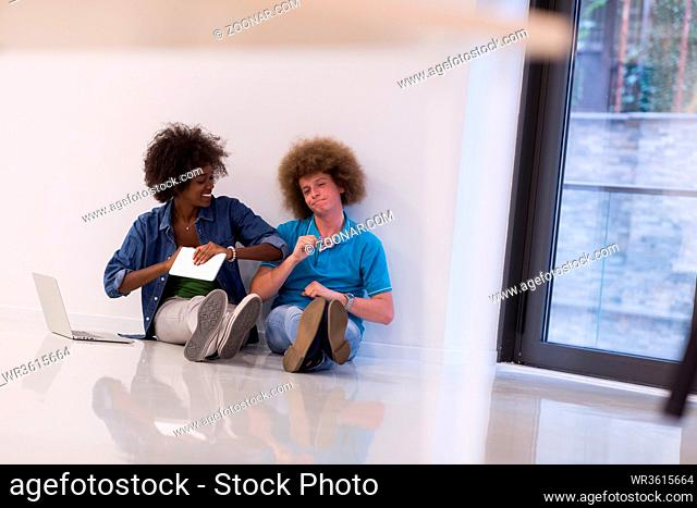 startup business and new mobile technology concept with young multiethnic couple in modern bright office interior working on laptop and tablet computer on new...